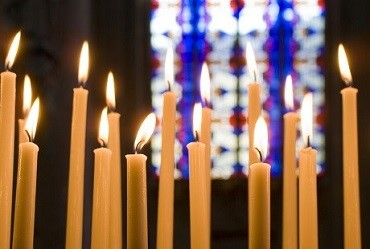 Image of candles in a church with stained glass in the backdrop